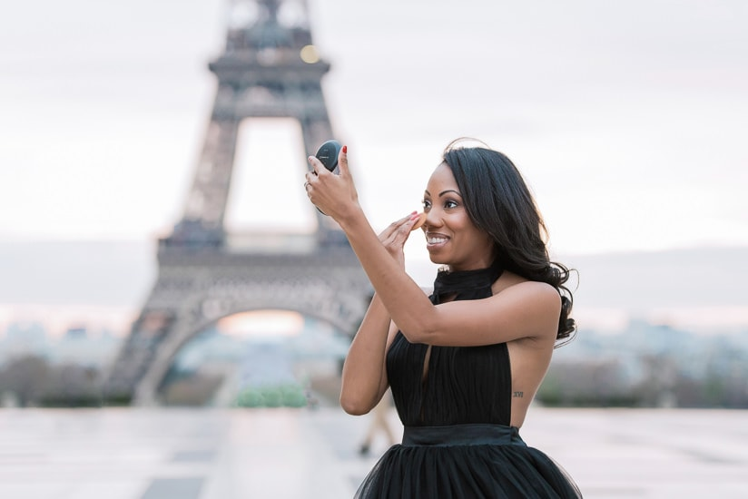Beautiful black girl getting ready to take Paris portraits at the Eiffel Tower