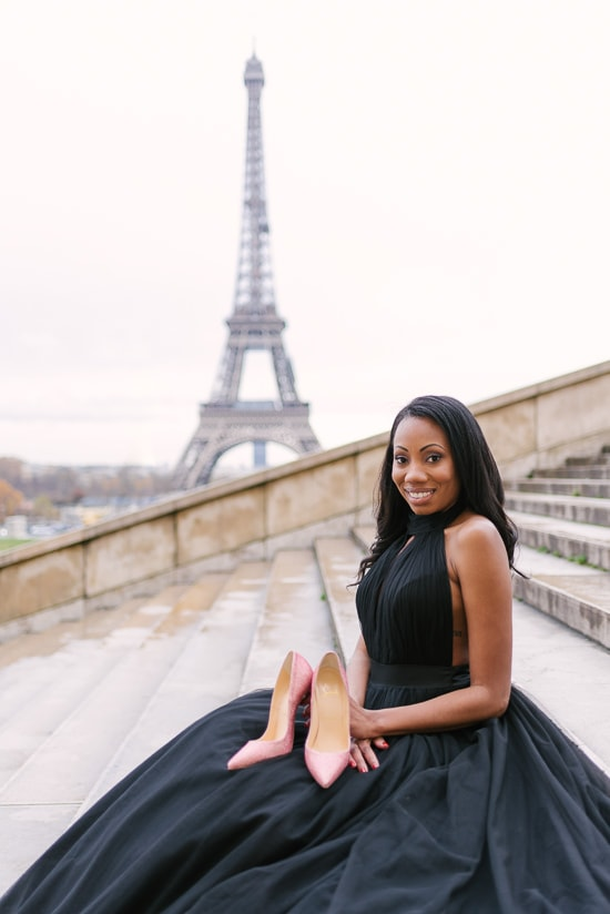 Beautiful black girl holding pink Louboutin high heels shoes in front of the Eiffel Tower in Paris