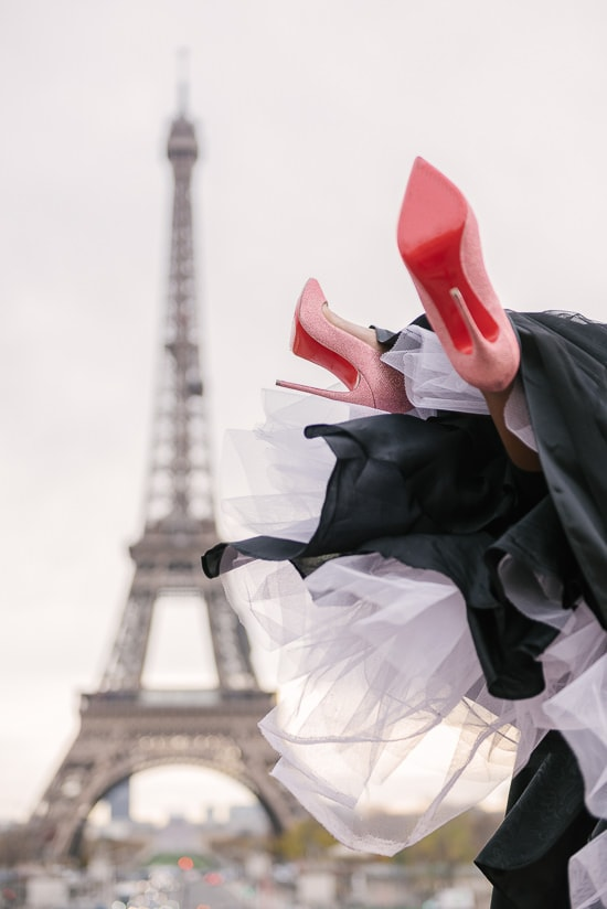 Christian Louboutin red soles lifted in the air at the Eiffel Tower in Paris