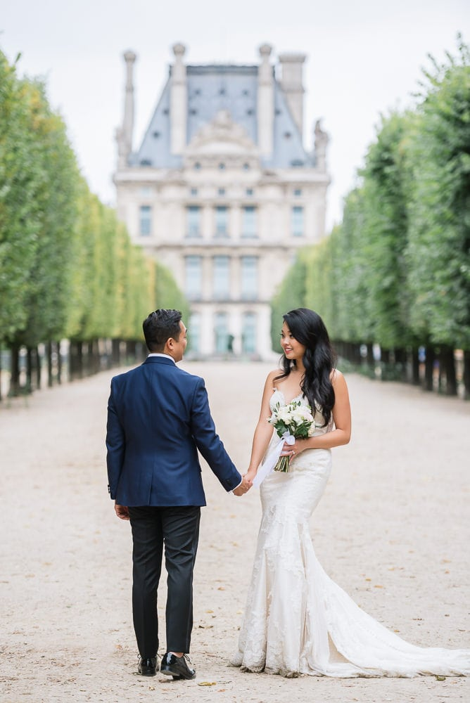 Elope to Paris in the Tuileries gardens. Bride and groom holding hands