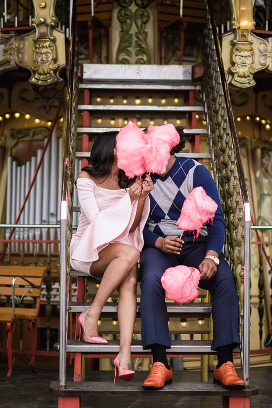 Girl with pink Louboutin heels kissing her boyfriend behind candy floss on the merry go round near Eiffel Tower