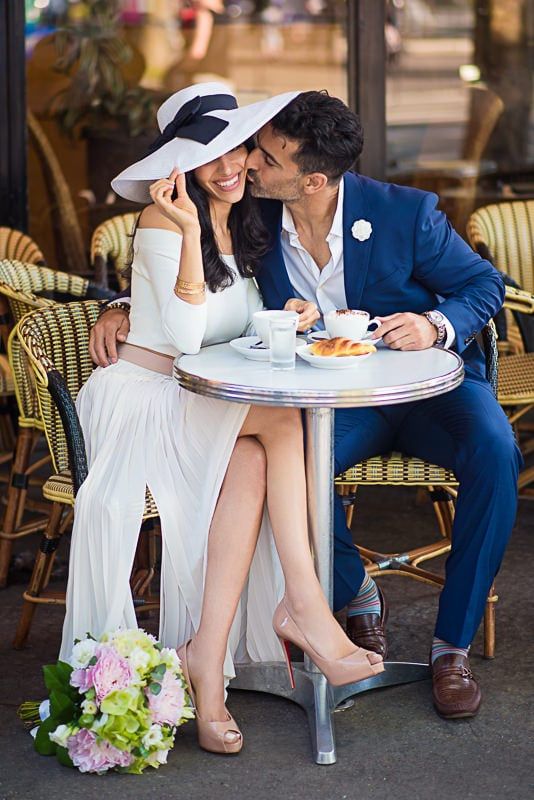Handsome gentleman kissing his fiancée on the cheek in a parisian café