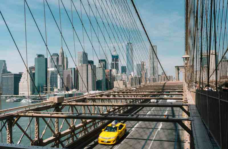 Taxi driving away from New York City on Brooklyn Bridge