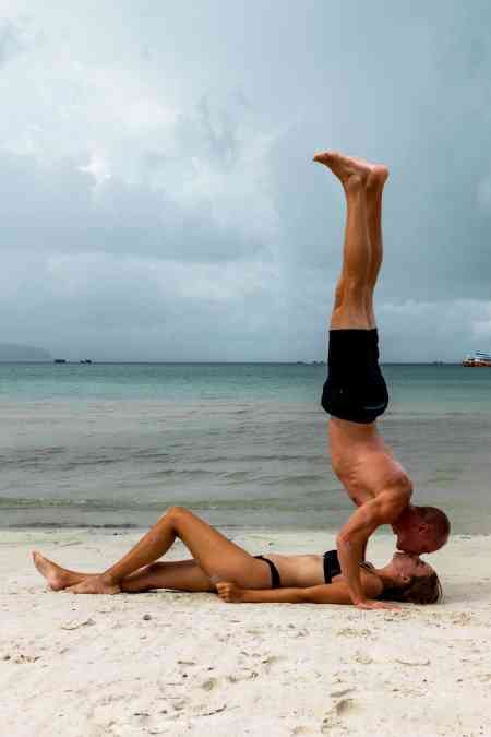 Nate doing Handstand over Alicia on beach in Cambodia