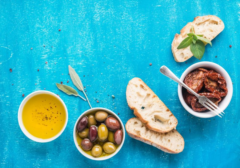 Mediterranean snacks set. Olives, oil, sun-dried tomatoes, herbs and sliced ciabatta bread on over blue painted background ( Photo: Shutterstock)