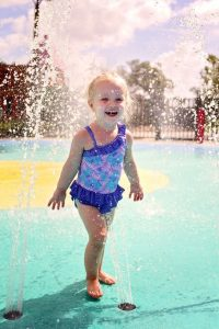 Little girl playing at splash pad