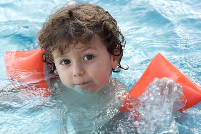 Little boy with floaties in pool