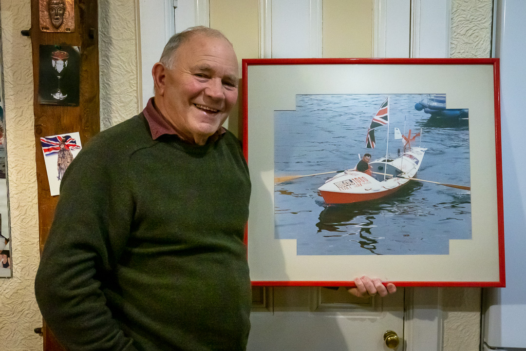 Adventurer Tom McClean, Holding a photo of his record-breaking row across the Atlantic Ocean in 1969, at his home in Morar. He'd just advised me of the best route on foot to reach his adventure centre at Ardintigh, where I'm aiming for the following night.