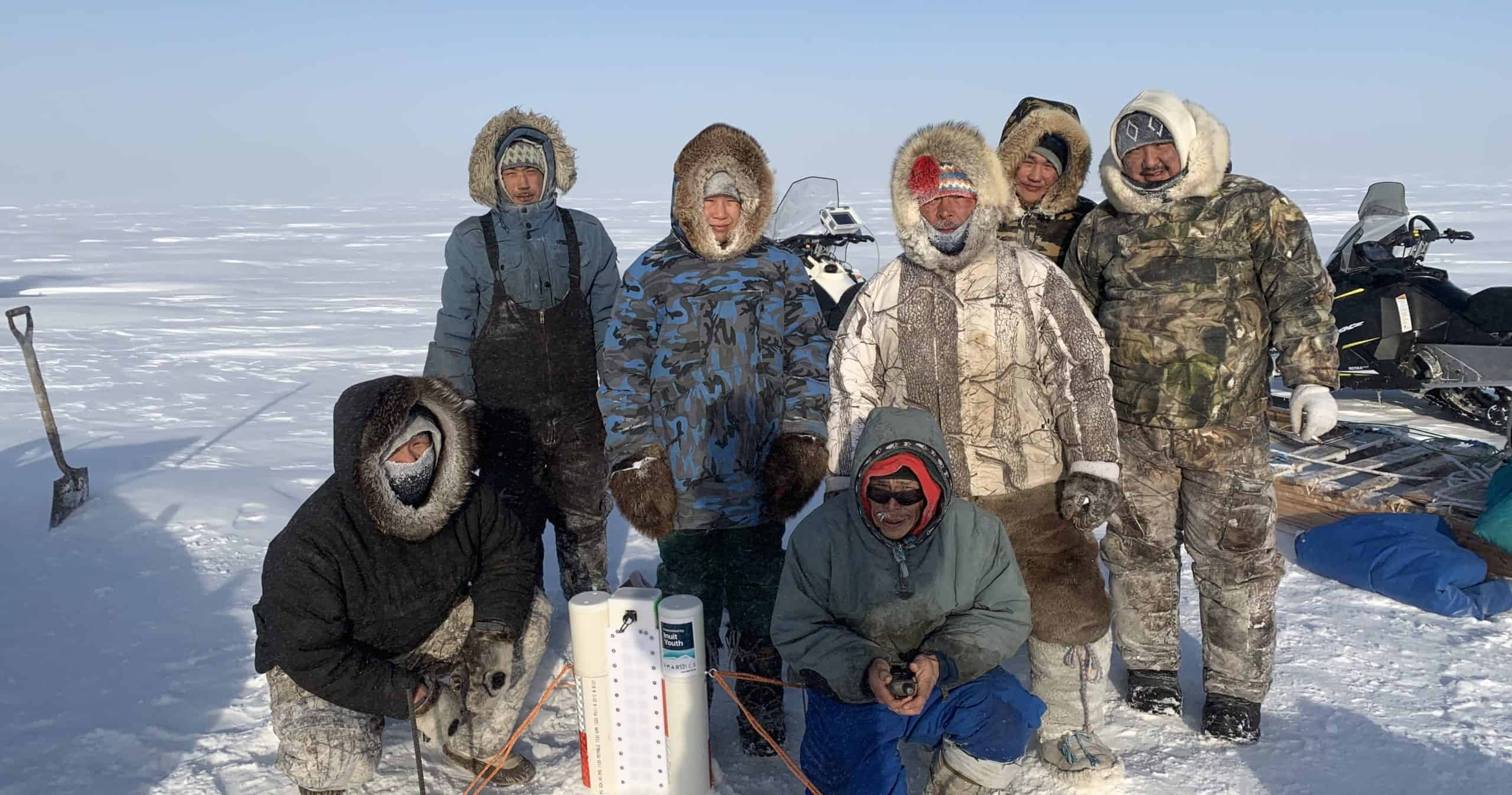 Image description: Seven community members and SmartICE operators in Igloolik, Nunavut are deploying a SmartBUOY device in the sea ice in March 2020. Data from the SmartBUOY is transmitted daily via satellite and made available to the community on SIKU.org.