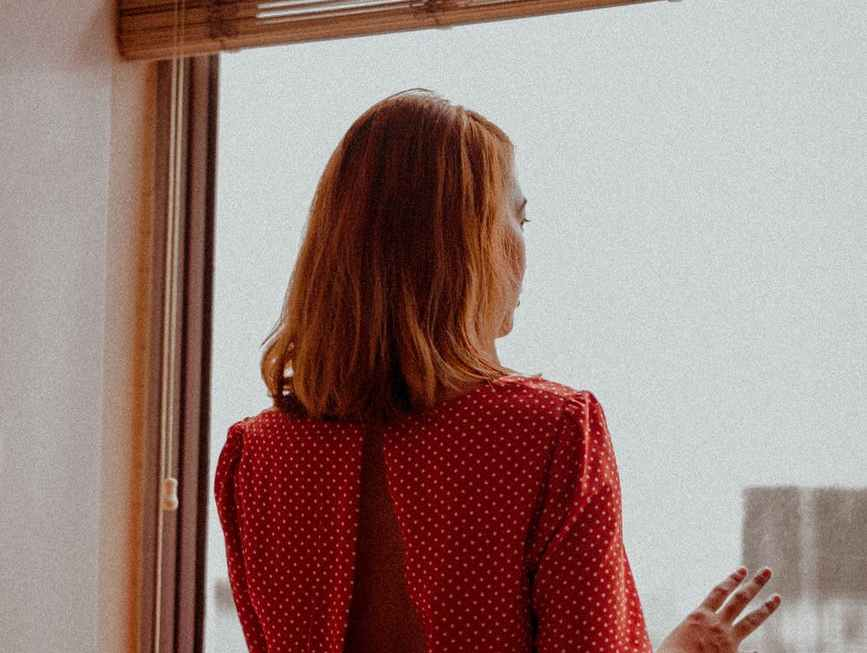 faceless woman looking out window at home