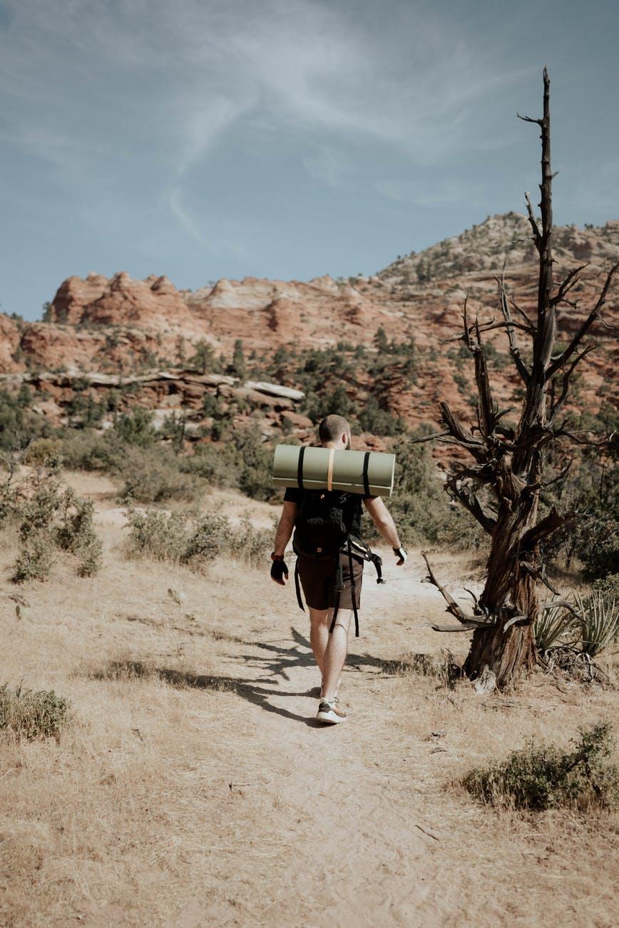 man backpacker walking in mountainous terrain