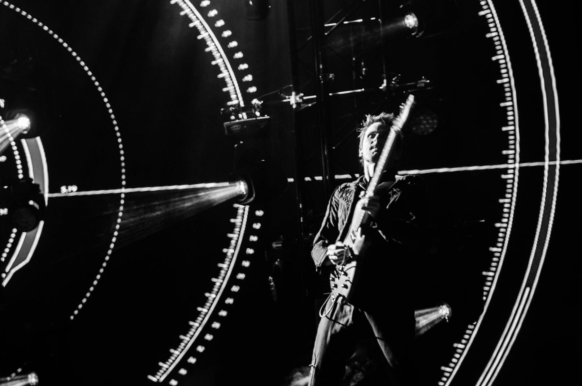 greyscale photography of man playing guitar