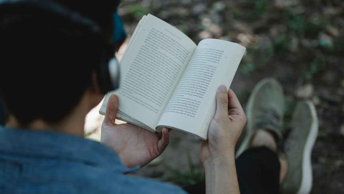 crop man in headphones reading book
