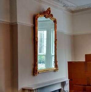 An ornate gilt framed mirror hung in a living room in Basingstoke.