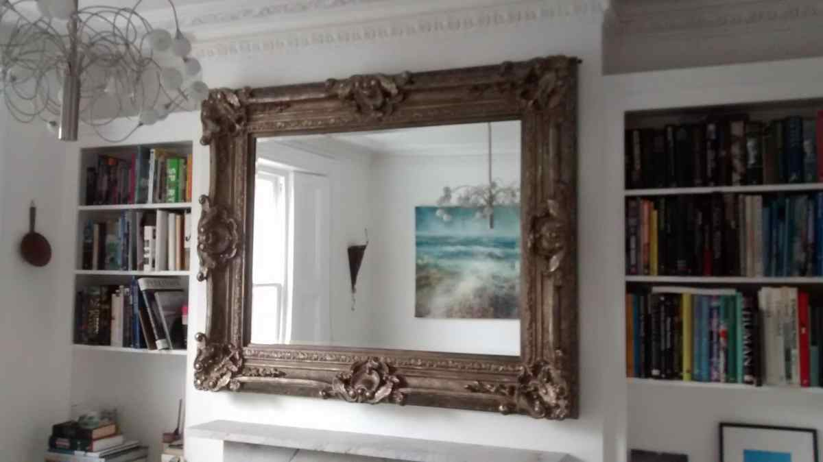 Large Baroque, wood-carved mirror, hung on a chimney breast that breaks up the shelves of books and adds depth to the living room.
