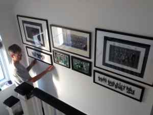 Our installer Scott Cowan making final adjustments to an arrangement of school photo frames above stairs in a house in Putney, West London.