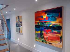 Two large abstract paintings hung on a white wall in a home in Horsham