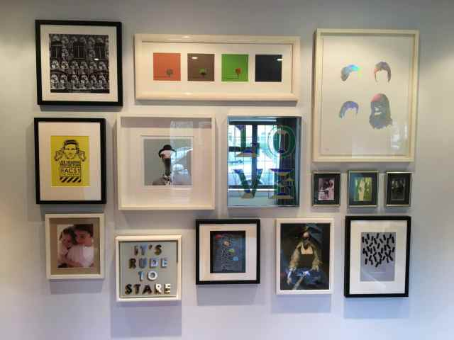 An asymmetric collage wall of frames, pictures, photos and mirrors hung on a wall in Buckhurst Hill, North East London
