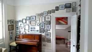 The client had made the wall of photos themselves over many years and it was all a bit wonky. They repainted the wall and asked us to rearrange the photos with the same cascade from right to left but without the wonk! So we did. Boom!