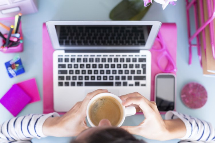 top view of a woman drinking a cup of coffee on a working desk - focus on the cup of coffee