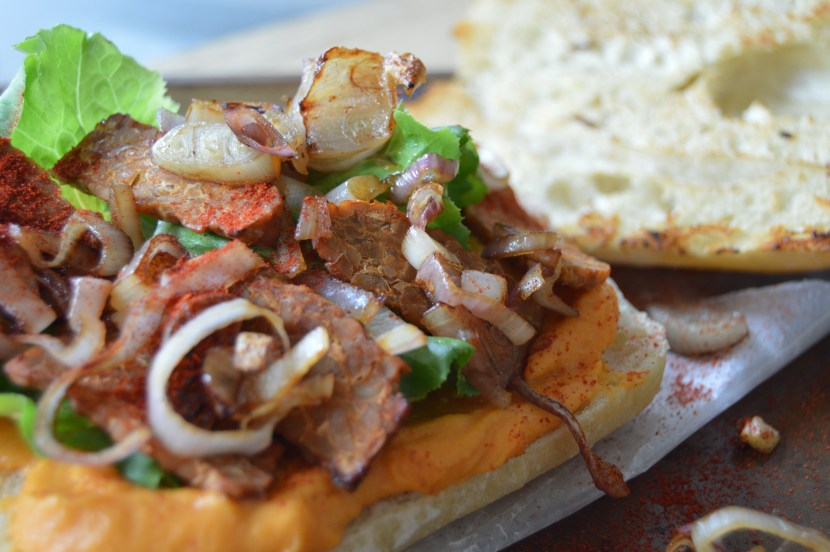 ciabatta sandwich with hummus and tempeh bacon close up