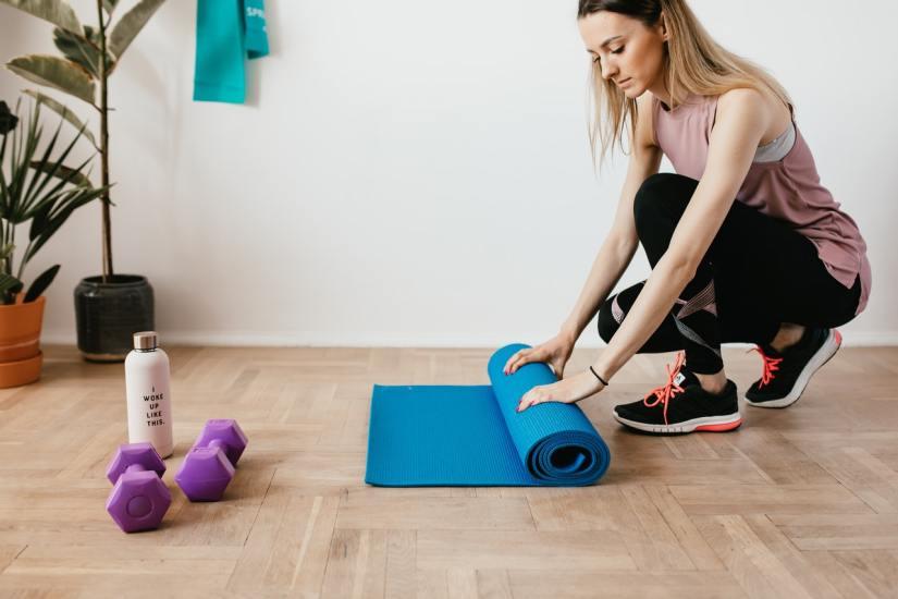 Fit sportswoman unfolding fitness mat on a floor