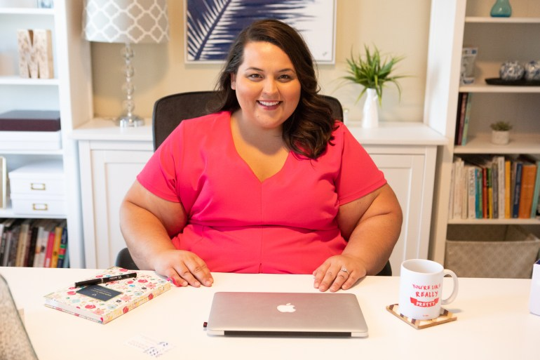 Miranda Schultz sitting at a desk in her home office wearing a pink dress.