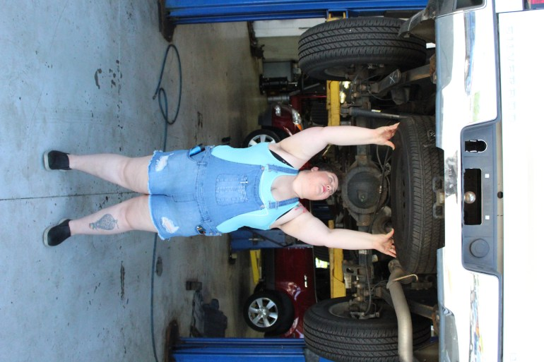 Chaya of Mechanic Shop Femme installs spare tire underneath vehicle in mechanic shop.