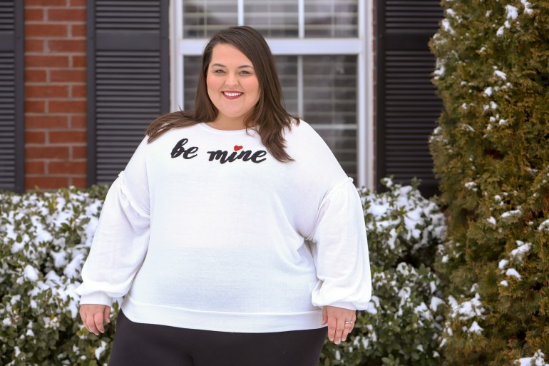 """Miranda Schultz of The Plus Life in a white sweater that reads, """"Be Mine."""""""
