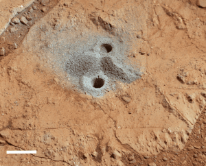 A Drill hole in the Yellowknife Bay, made by the Mars Curiosity rover. The drill hole is 1.6 cm in diameter, and the white scale bar at the bottom right of this picture is 2 cm in length (Photo Credit: University of Leicester).