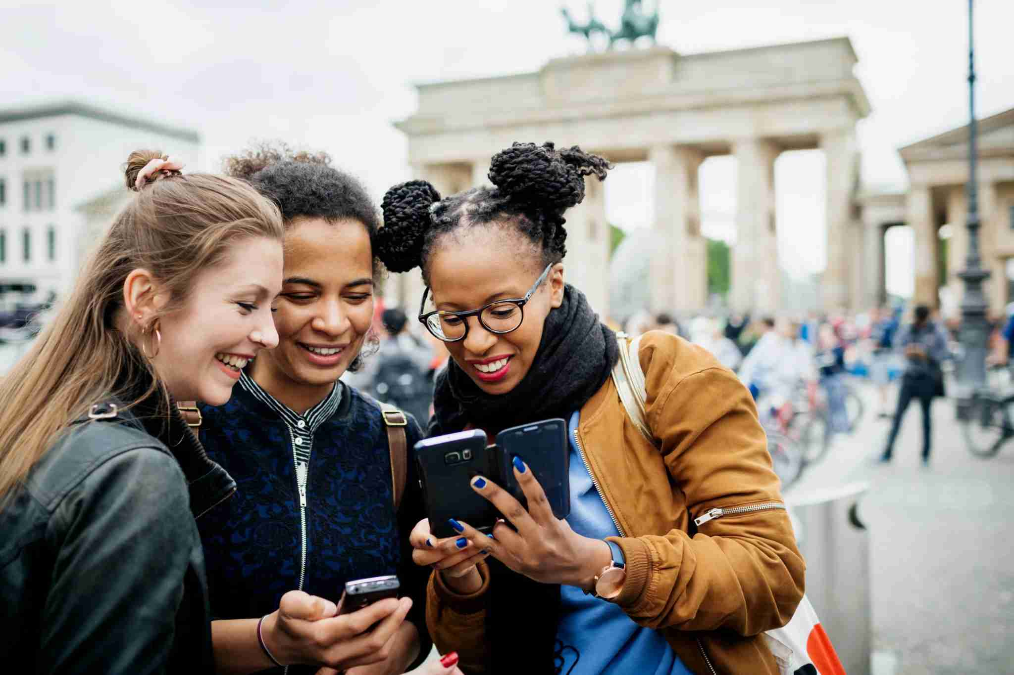 A group of friends travelling together are exploring the local tourist attractions and architecture, they stop for a moment to look over recent photos on their phones. Photo by Hinterhaus Productions/Getty
