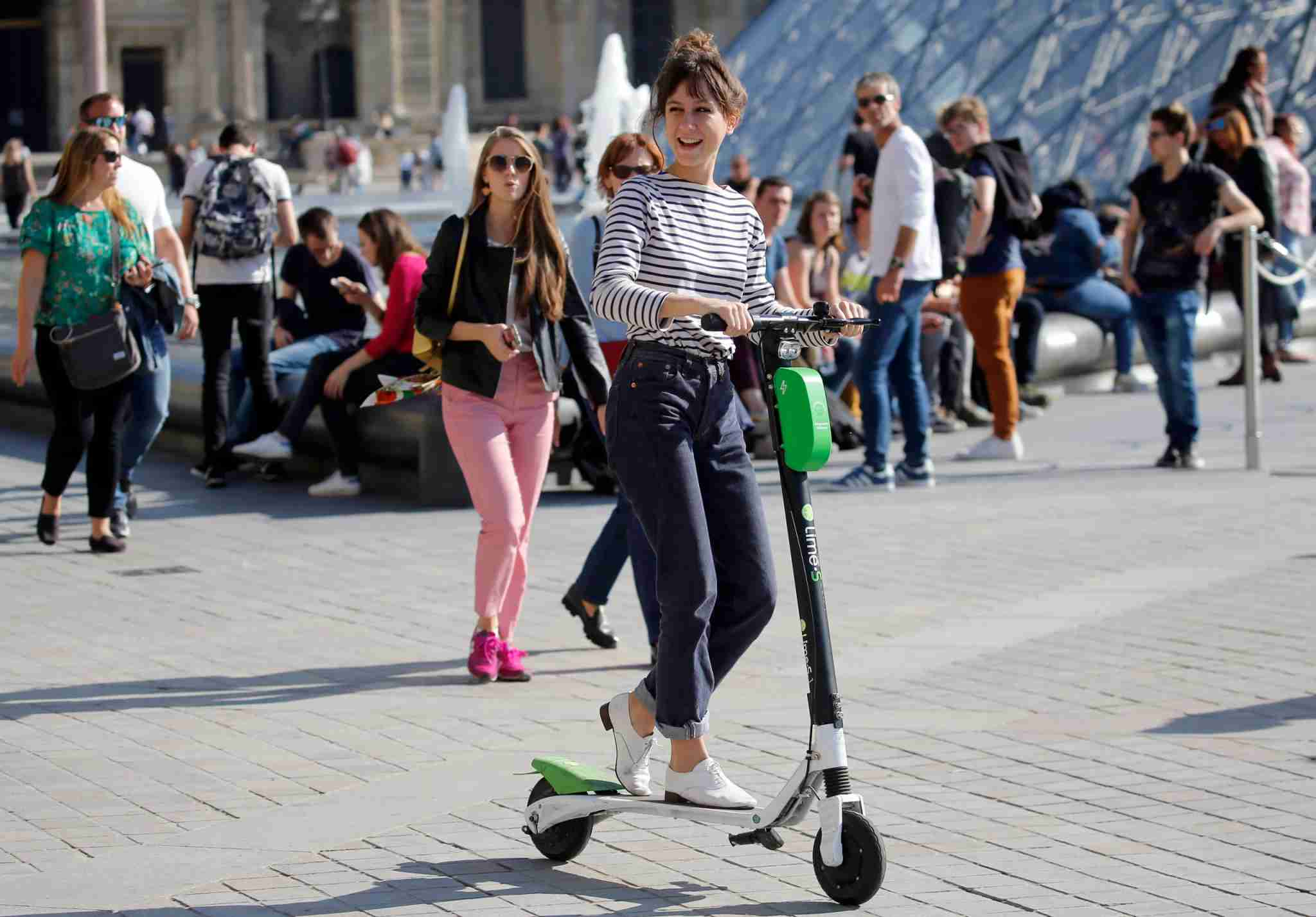 PARIS, FRANCE - OCTOBER 09: A woman rides an electric scooter Lime-S from the bike sharing service company