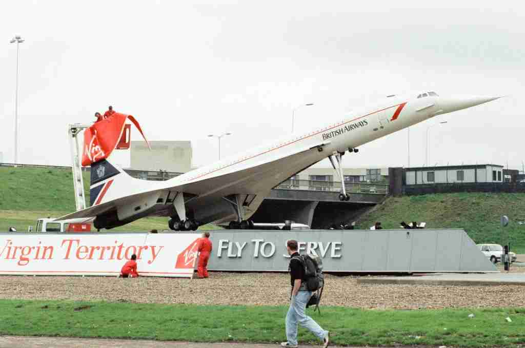Virgin Group staff hijacking the British Airways Concorde model that stands at the entrance to the tunnel and changed the livery to Virgi on the day the first Virgin airways flight arrived at Heathrow, 1st July 1991. (Photo by Victor Crawshaw /Mirrorpix/Getty Images)