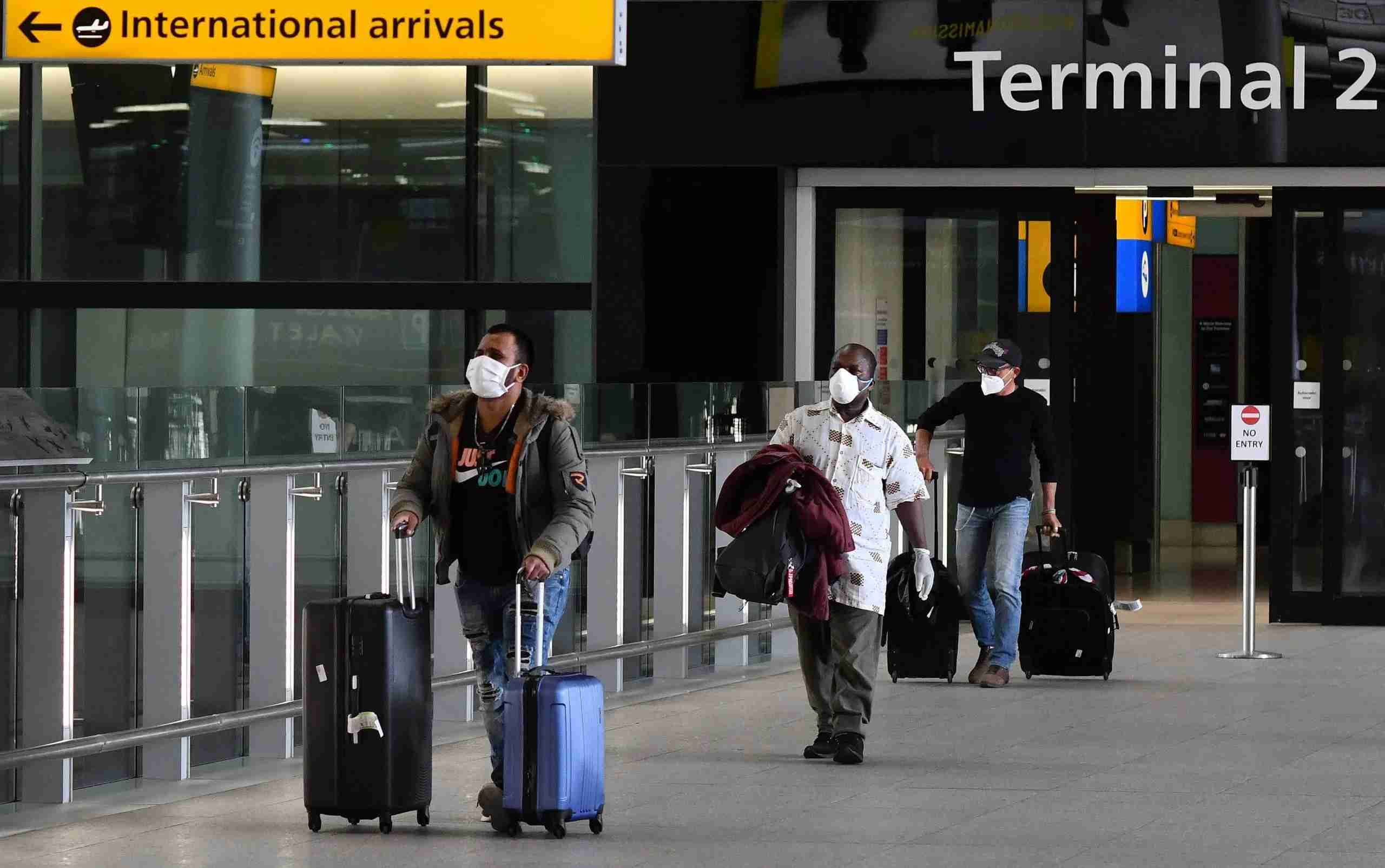 Passengers wearing PPE (personal protective equipment), including a face mask as a precautionary measure against COVID-19, walk through the arrivals hall after landing at at Terminal Two of London Heathrow Airport in west London, on May 9, 2020. - Britain could introduce a 14-day mandatory quarantine for international arrivals to stem the spread of coronavirus as part of its plan to ease the lockdown, an airline association said Saturday, sparking alarm in an industry already badly hit by the global pandemic. (Photo by JUSTIN TALLIS / AFP) (Photo by JUSTIN TALLIS/AFP via Getty Images)