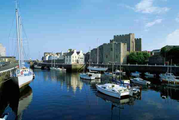 View of boats docked at a harbor, Rushen Castle, Isle of Man, British Isles. Photo by Medioimages / Photodisc / Getty Images