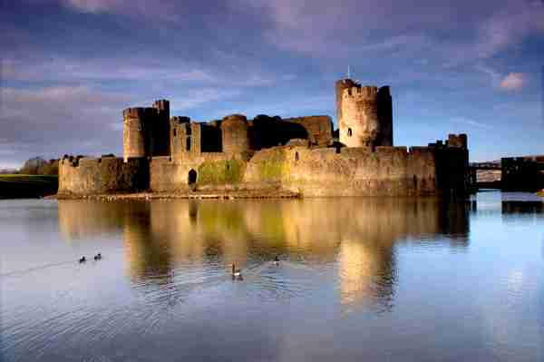 Caerphilly Castle, and reflection in the moat. Photo by Momodine / Getty Images