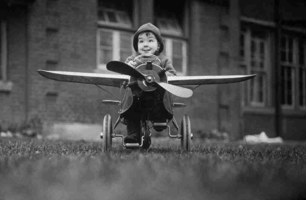 2nd October 1934: A child from Aldersbrooke Home in Essex setting off for a trip in a model aeroplane. (Photo by J. A. Hampton/Topical Press Agency/Getty Images)