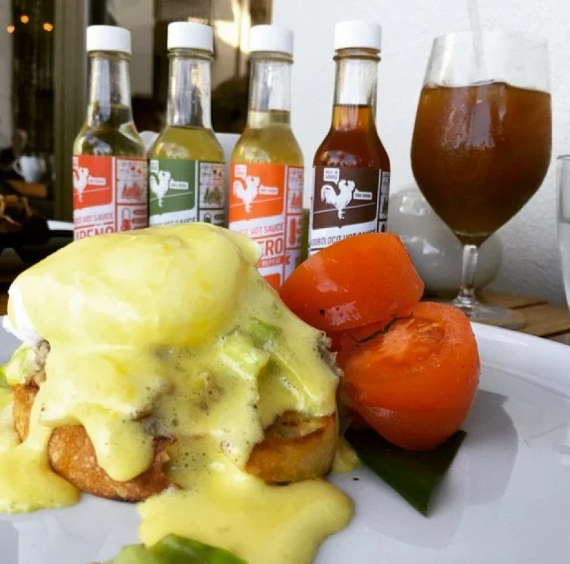 A volcanic eruption of the taste buds - Kalua Pork Benedict with ponzu hollandaise and heirloom tomato salad topped with Thai pepper hot sauce