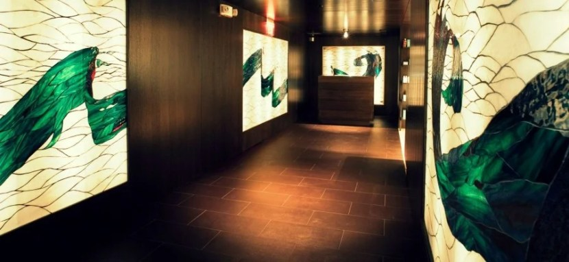 The dark wood and wall art of the White Orchid Spa's entrance hints at the relaxation to come.