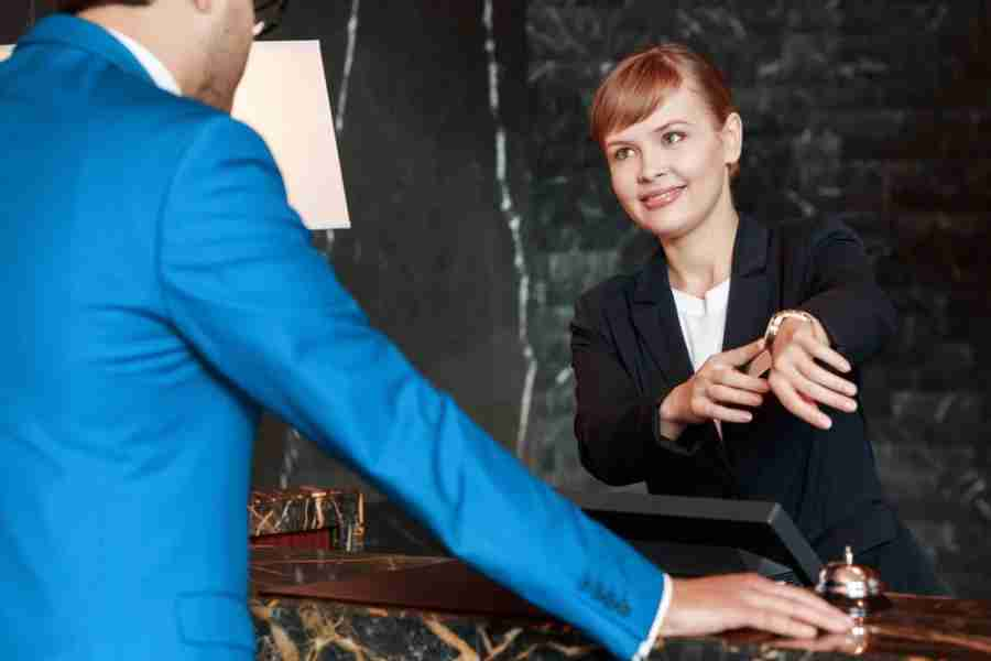 Sure, the cheerful front desk manager will smile at you, but you may still be charged for your late check-out. Photo courtesy of Shutterstock.