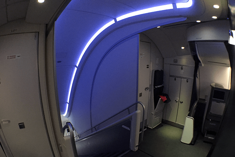 The blue-lit stairway toward the front of the plane