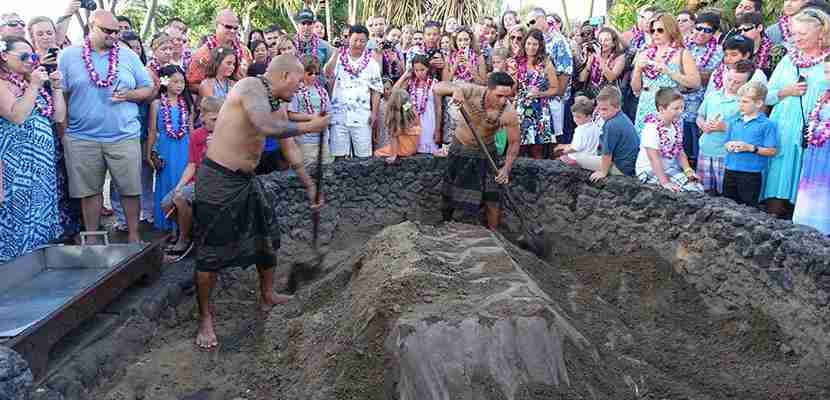 The kalua pig is unveiled in front of a crowded at the luau.