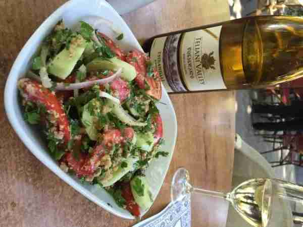 Cucumber and tomato salad served with crushed walnuts and a delicious bottle of Tsinandali.