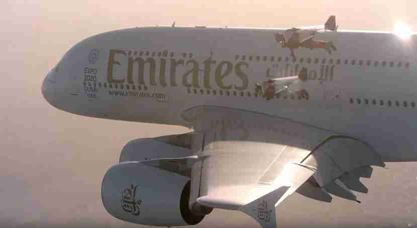 An Emirates A380 flying to two jetpacks.