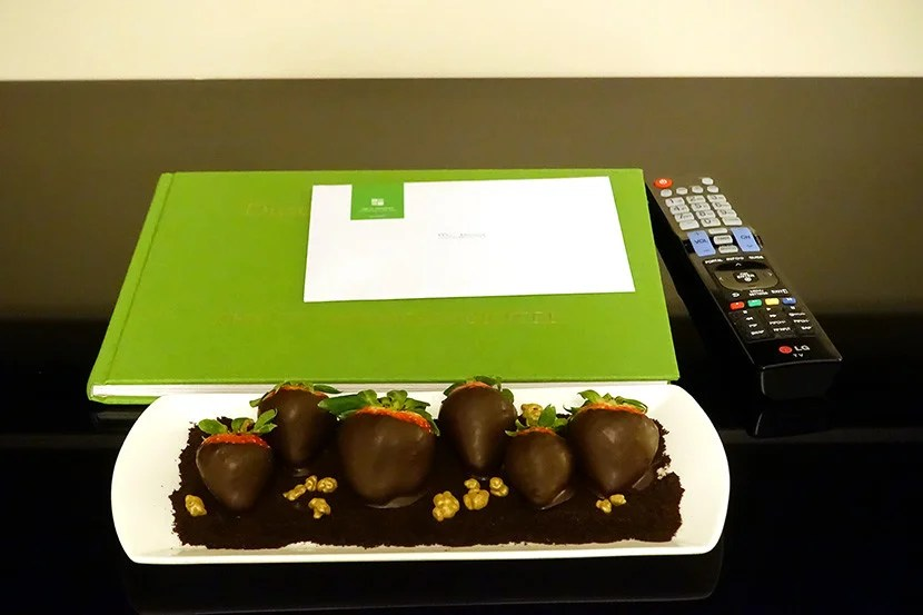 A welcome gift of chocolate-covered strawberries, set next to a book about the hotel's history.