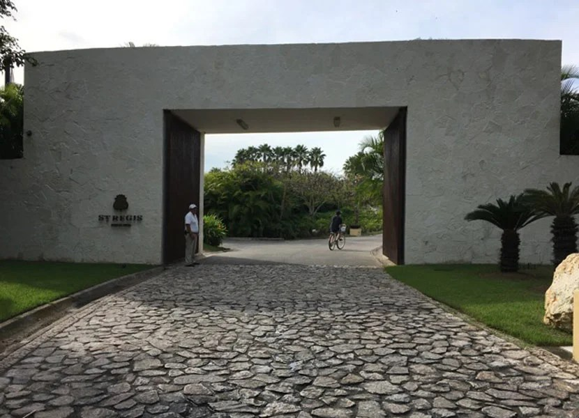 the cobblestone driveway and gate leading to the resort