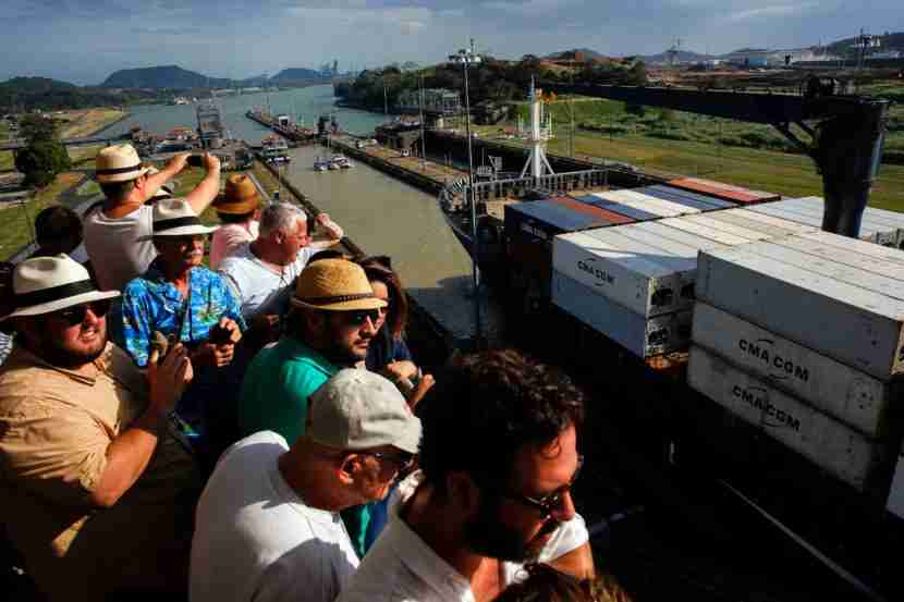 Visitors, many sporting their Panama hats, watch as a container ship passes through the Miraflores locks.