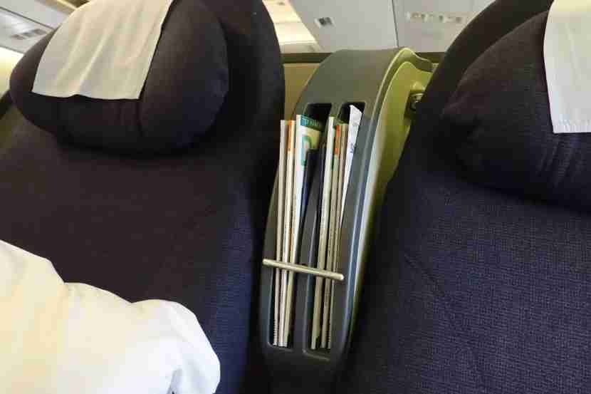 Magazines and other reading materials are stored between the seats.
