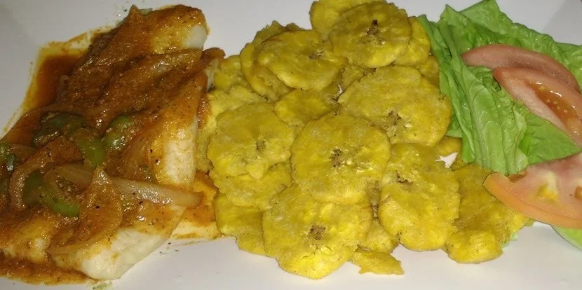 Grilled grouper in Creole sauce with of <em>tostones</em> and salad.