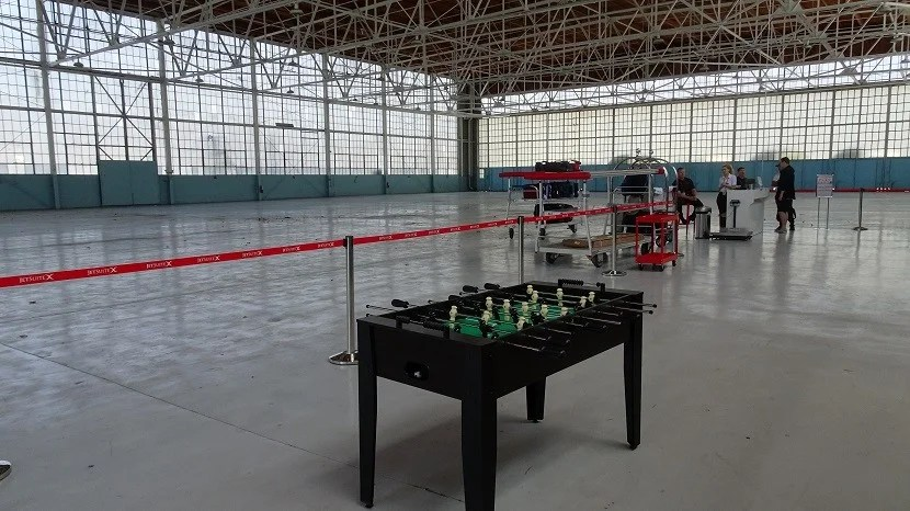 The roomy hangar functions as check-in counter, baggage claim, and Foosball stadium.
